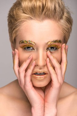 beautiful girl with golden glittering makeup touching face isolated on grey