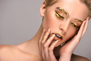 sensual attractive woman with golden makeup touching face isolated on grey