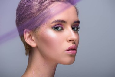 attractive woman with violet makeup looking at camera isolated on grey