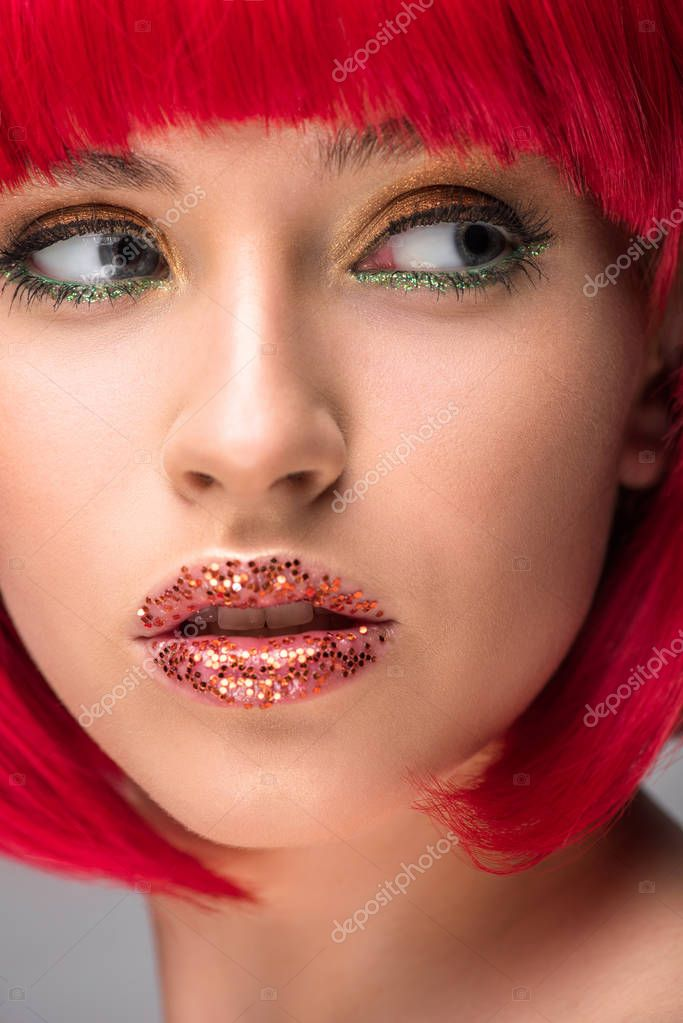 headshot of attractive woman with red hair and glitter on face looking away