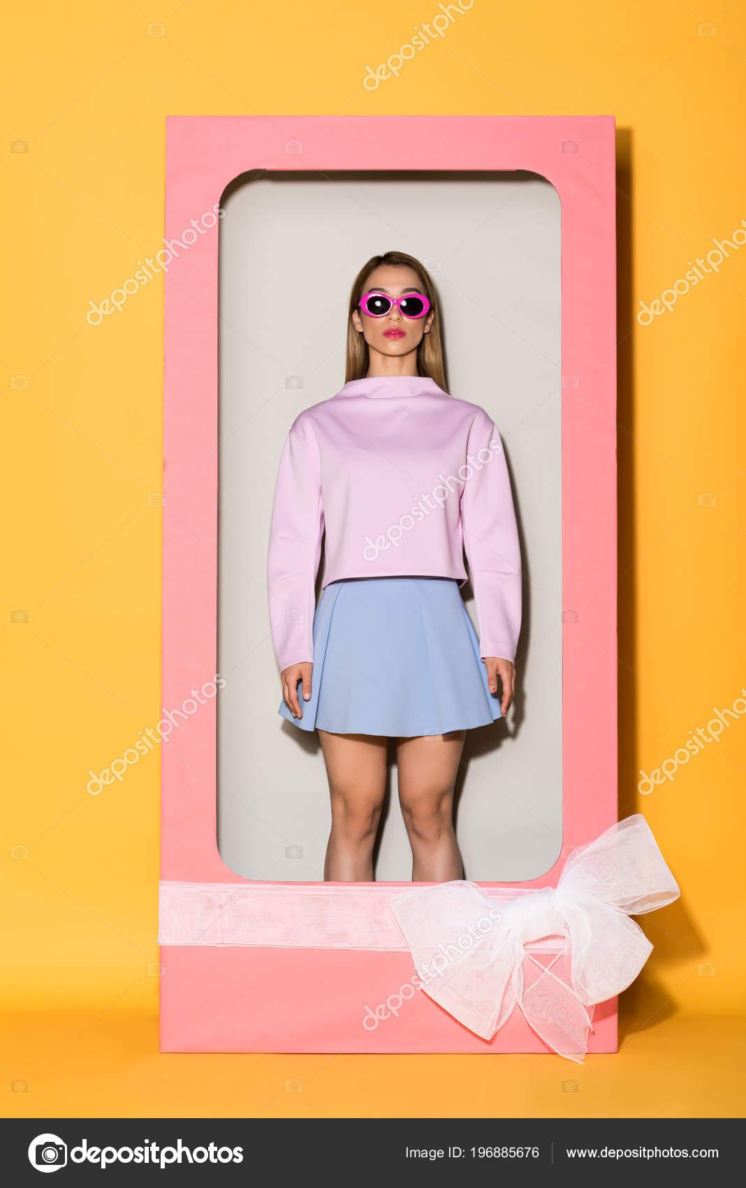 e265638749 Νέοι κομψό γυναικείο πρότυπο για γυαλιά ηλίου σε διακοσμητικό κουτί με  φιόγκο σε κίτρινο φόντο — Εικόνα από ...