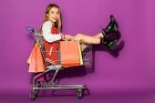gyönyörű ázsiai nő, bevásárló táskák, bevásárló kocsi, és a kamera a lila mosolyogva ül