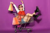 krásná šťastná mladá žena v sluneční brýle drží papírové tašky a sedí v nákupní vozík na fialové