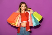 Fotografie attractive asian girl with shopping bags holding credit card and smiling at camera isolated on violet