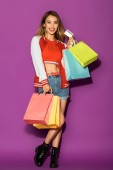 Photo happy asian girl with shopping bags holding credit card and smiling at camera isolated on violet