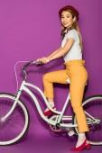 po celé délce pohled šťastné stylová Asijská dívka jízda kole a usmívá se na kameru izolované na fialové