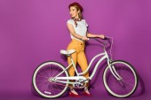 full length view of beautiful smiling stylish asian girl standing with bike and looking away isolated on violet