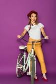 po celé délce pohled krásná stylová žena stojící kolo a usmívá se na kameru izolované na fialové