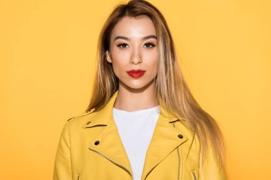 portrait of young stylish asian woman isolated on yellow background