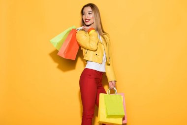 asian young woman with shopping bags on yellow background