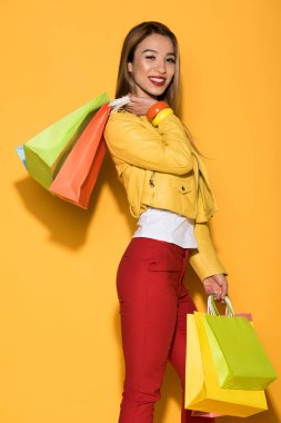 happy asian female shopaholic with paper bags on yellow background