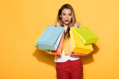 female asian shopper with paper bags standing on yellow background