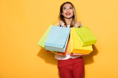 happy female shopper standing with paper bags on yellow background