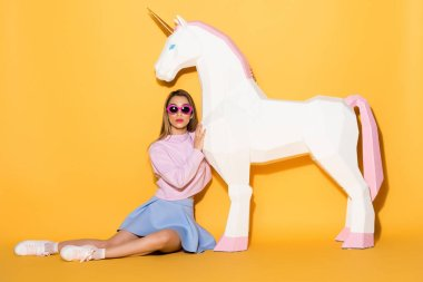 young female model in sunglasses sitting on floor and embracing decorative unicorn on yellow background
