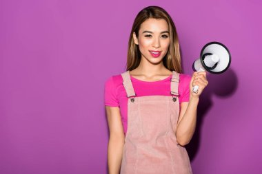 attractive asian female model with megaphone on purple background
