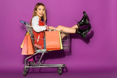 beautiful asian woman with shopping bags sitting in shopping trolley and smiling at camera on violet
