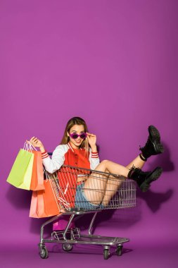beautiful asian girl with paper bags sitting in shopping trolley and smiling at camera on violet