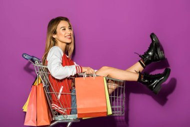 beautiful smiling asian girl with paper bags sitting in shopping trolley and looking away on violet