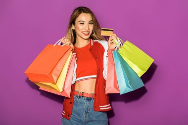 attractive asian girl with shopping bags holding credit card and smiling at camera isolated on violet