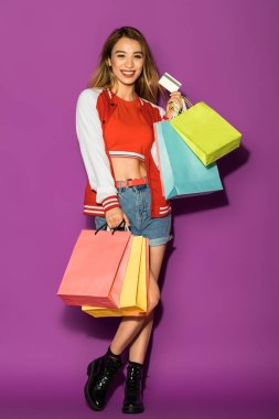 happy asian girl with shopping bags holding credit card and smiling at camera isolated on violet