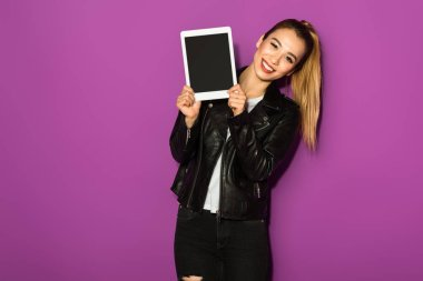 beautiful young woman holding digital tablet and smiling at camera isolated on violet