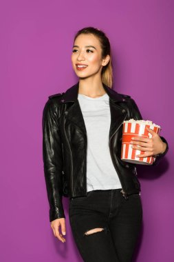 beautiful smiling asian girl in leather jacket holding popcorn and looking away isolated on violet