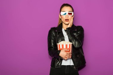 shocked young woman in 3d glasses eating popcorn and looking at camera isolated on violet