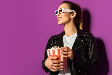 beautiful smiling asian girl in 3d glasses holding popcorn and looking away isolated on violet