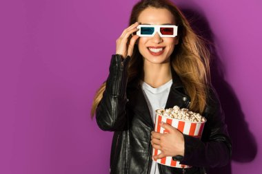 Beautiful young woman in 3d glasses holding box of popcorn and smiling at camera isolated on violet stock vector