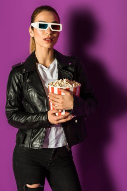 Beautiful stylish girl in leather jacket and 3d glasses holding popcorn on violet stock vector