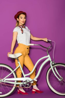Full length of beautiful stylish asian woman standing with bike and smiling at camera isolated on violet stock vector