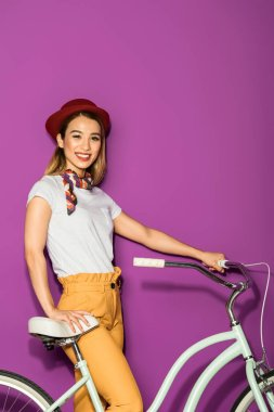 beautiful young asian woman standing with bicycle and smiling at camera isolated on violet