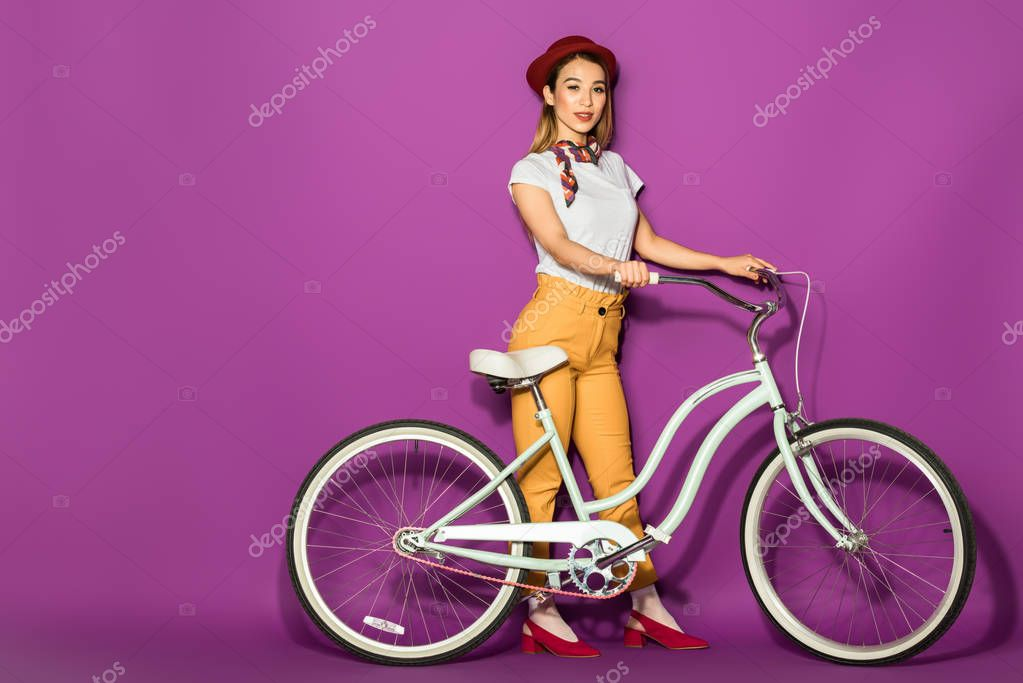 beautiful stylish asian girl standing with bike and smiling at camera isolated on violet