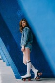 boční pohled na usmívající se žena v džínové oblečení, vysoké ponožky a retro kolečkové brusle