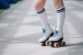 Fotografie partial view of woman in white high socks and retro roller skates