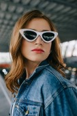 Photo portrait of young fashionable woman in denim clothing and retro sunglasses