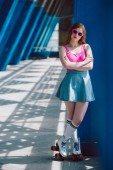 Fotografie beautiful girl in sunglasses, denim skirt and roller skates standing with crossed arms and looking at camera