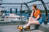 Fotografie boční pohled zamyšlená dívka v uhýbaje kolečkové brusle při sezení poblíž řeky