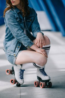 partial view of stylish woman in denim clothes, high socks and retro roller skates