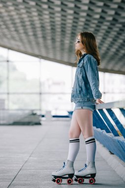 side view of stylish woman in denim clothing, high socks and retro roller skates
