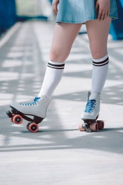 partial view of woman in white high socks with black stripes and retro roller skates
