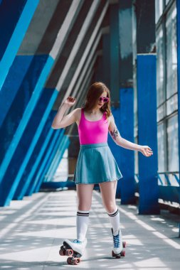 young woman in stylish clothing and retro sunglasses roller skating alone