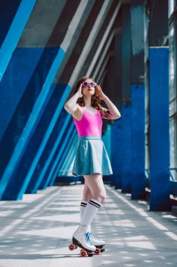 full length view of stylish girl in vintage roller skates looking up on street