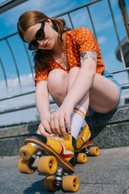 low angle view of stylish girl in sunglasses wearing roller skates on street