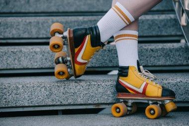 cropped shot of girl on girl wearing roller skates on street