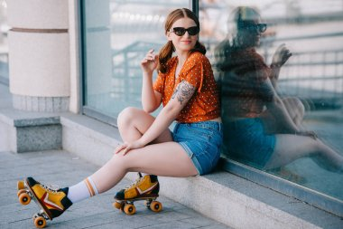 beautiful girl in sunglasses and roller skates smiling at camera while sitting on street