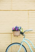 Photo close-up view of bicycle with beautiful colorful flowers in basket near wall