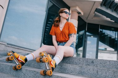 low angle view of stylish girl in roller skates sitting on stairs and looking away