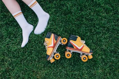 cropped shot of female legs in socks and vintage roller skates on green grass