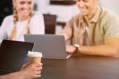 levágott szemcsésedik-ból laptop és papír kávé asztalnál ülő üzletember kupa, miközben dolgozik mögött mosolygó kollégái